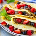 A plate of four crepes that are filled with nutella, strawberries, blueberries and raspberries.