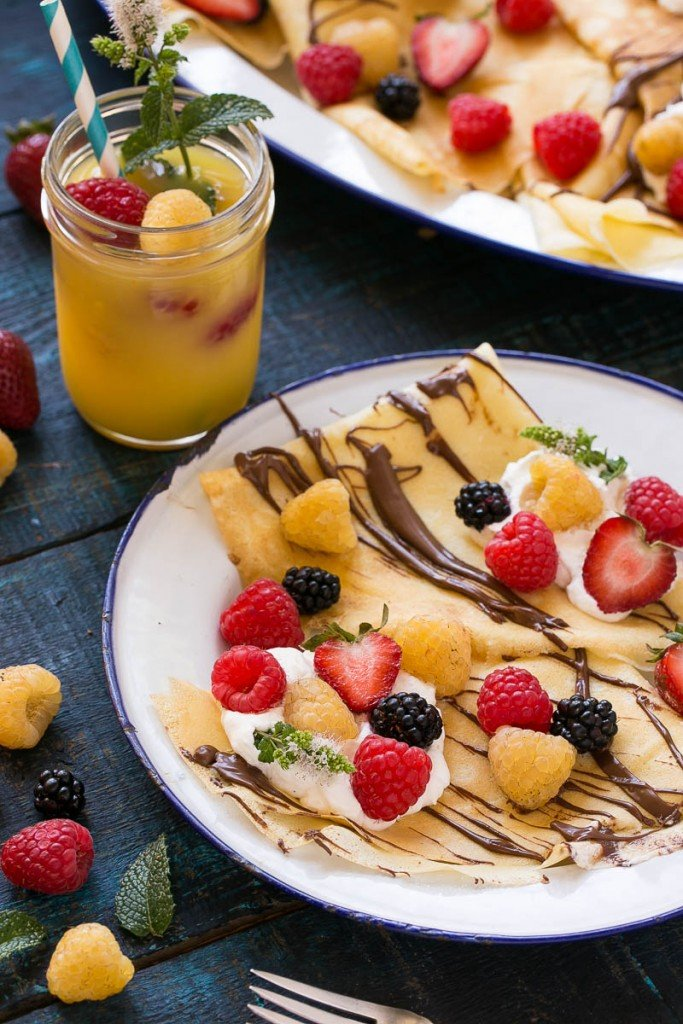 These nutella berry crepes are a foolproof recipe for blender crepes topped with nutella, whipped cream and fresh berries.