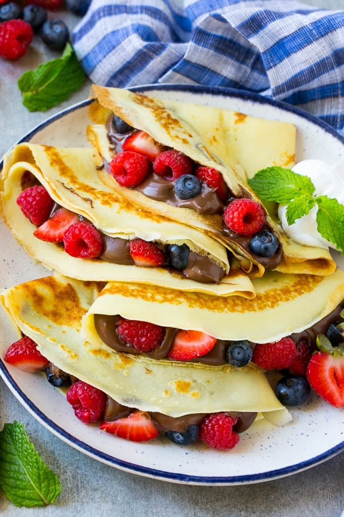 A platter of crepes that have been stuffed with nutella and berries, served with whipped cream.