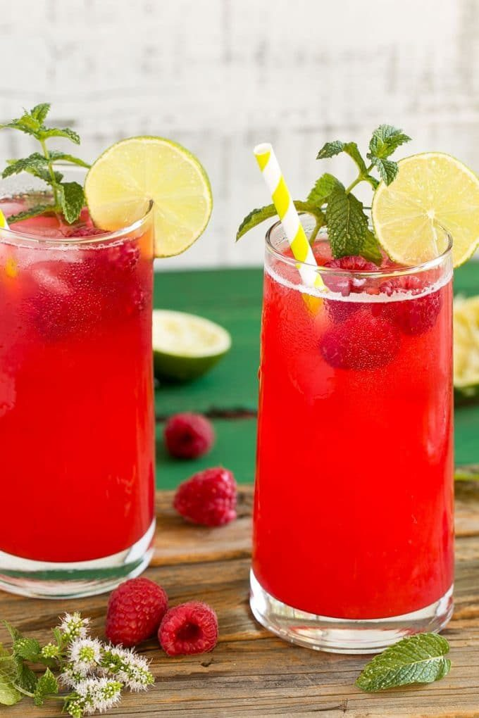 Glasses of raspberry limeade garnished with mint and limes.