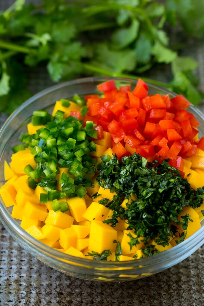 Diced mango, jalapeno, red pepper and cilantro in a bowl.