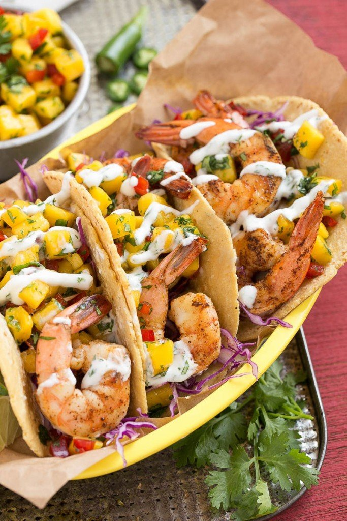 Shrimp tacos with sweet and tangy mango salsa and creamy cilantro lime sauce.
