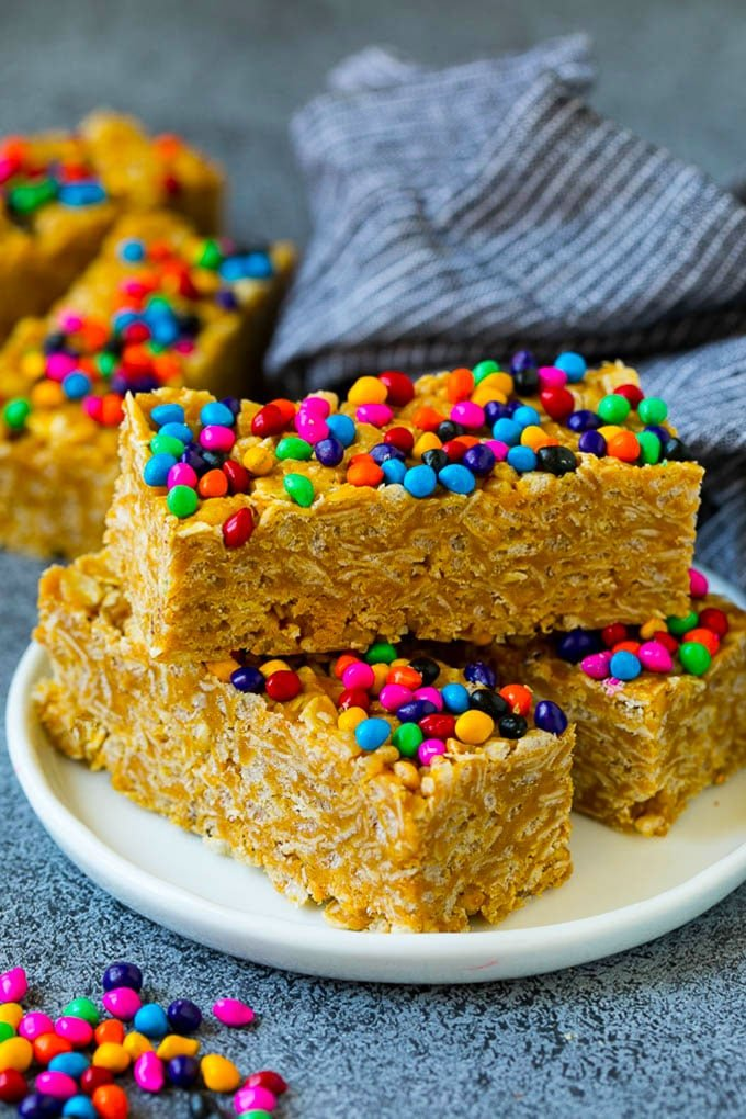 Cereal bars on a plate with colorful candy coated chocolates on top.