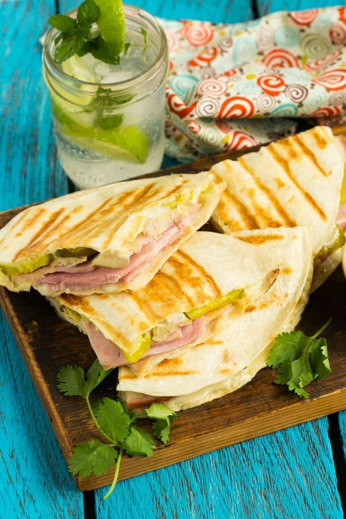 A cuban sandwich in quesadilla form with roasted pork, smoked ham, pickles and plenty of cheese in between grilled tortillas.