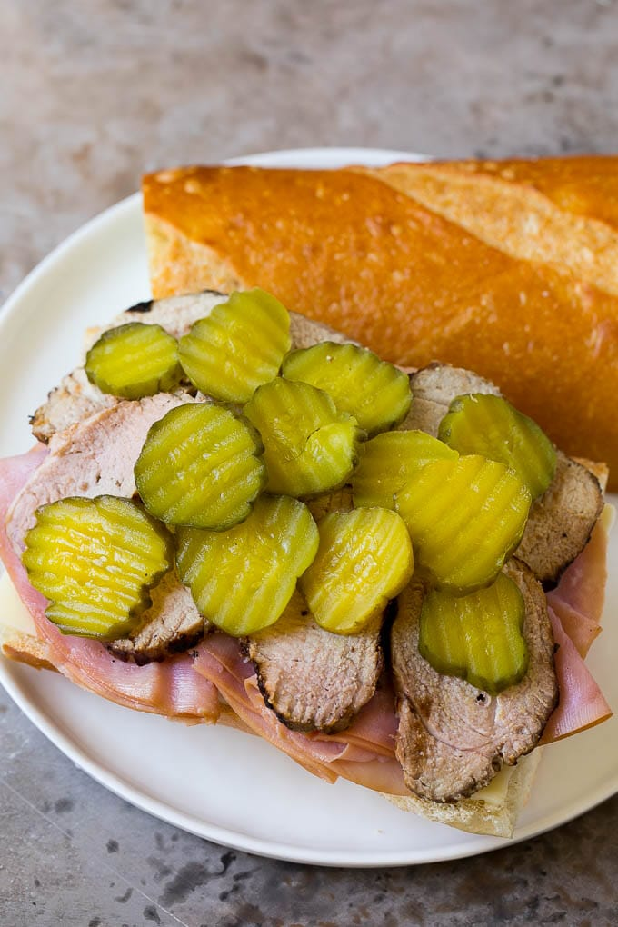 Pork, ham, cheese and pickles on a roll.