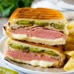 A pressed Cuban sandwich with layers of ham, cheese and pickles.