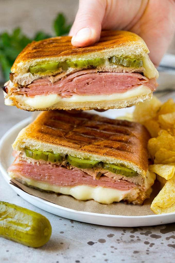 A hand holding up half of a Cuban sandwich.