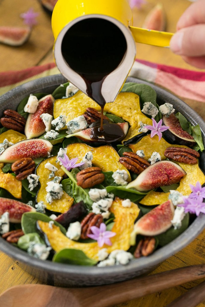 This spinach salad recipe is full of figs, roasted acorn squash, candied pecans and blue cheese and is finished off with a honey balsamic dressing.