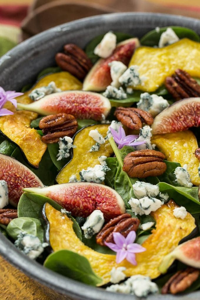 Spinach salad topped with fresh figs, roasted squash, nuts and cheese.
