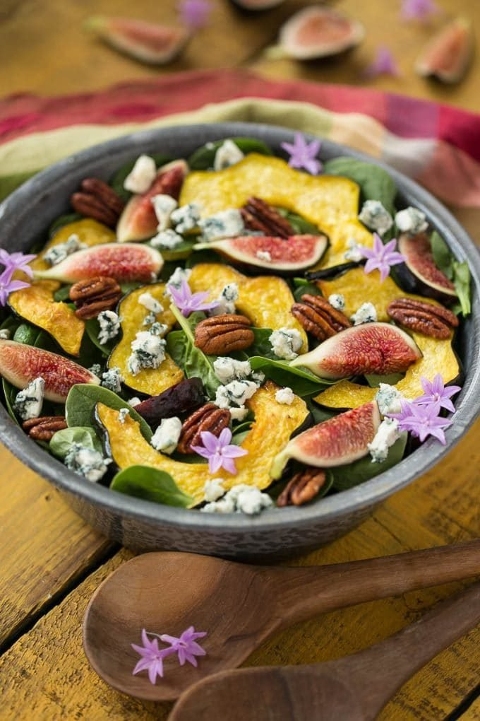 A bowl filled with spinach, fig and pecan salad.