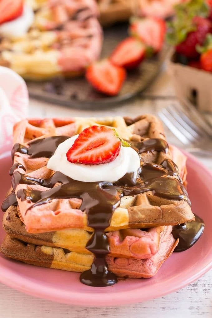 A stack of neopolitan waffles topped with chocolate sauce and berries.
