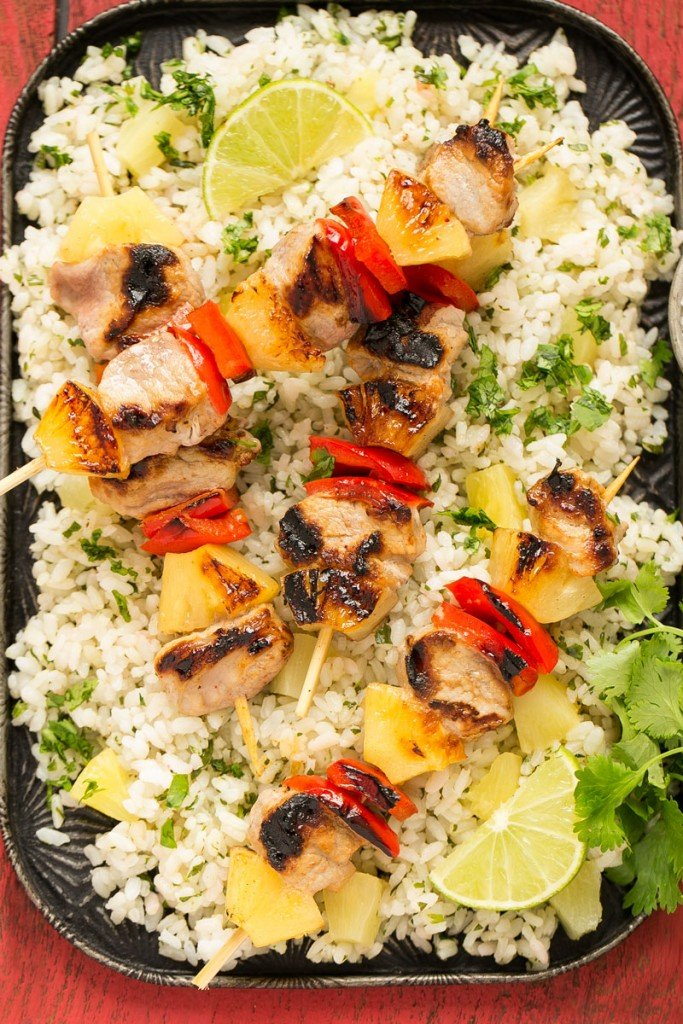 A recipe for sweet and spicy pineapple pork kebabs served on a bed of pineapple cilantro rice.