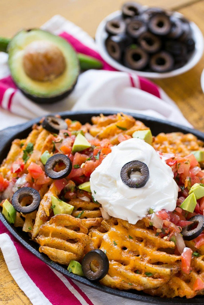 Waffle fries are smothered in nacho toppings for a fun and delicious snack.
