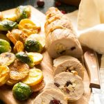 Apple cranberry stuffed pork tenderloin, potatoes and brussels sprouts all cooked together on one pan.