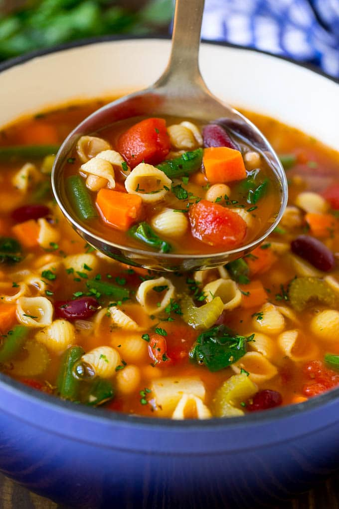 A ladle serving up a portion of classic minestrone soup.