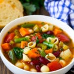 A bowl of minestrone soup made with vegetables and beans, served with a side of bread.