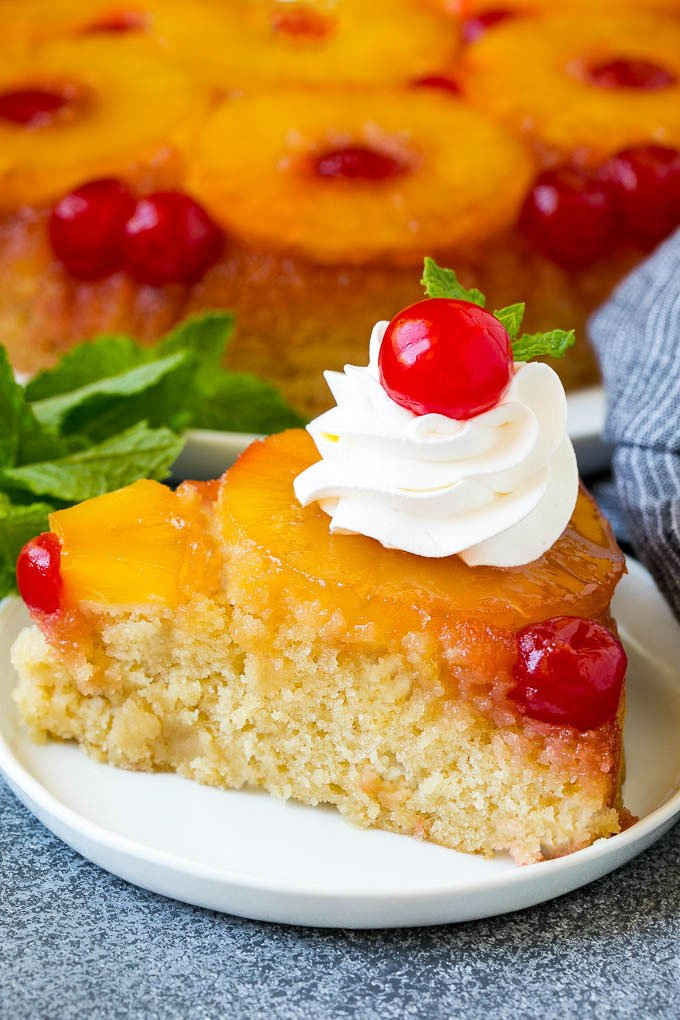 A slice of pineapple upside down cake topped with whipped cream and a cherry.