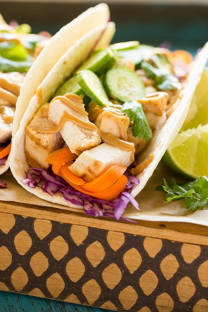 These thai chicken tacos are a quick and easy dinner. Coconut marinated chicken is stuffed into warm tortillas with fresh vegetables and a generous amount of homemade peanut sauce.