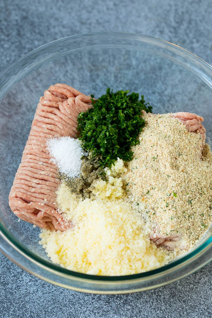 Ground turkey with breadcrumbs, herbs, seasonings and cheese in a bowl.