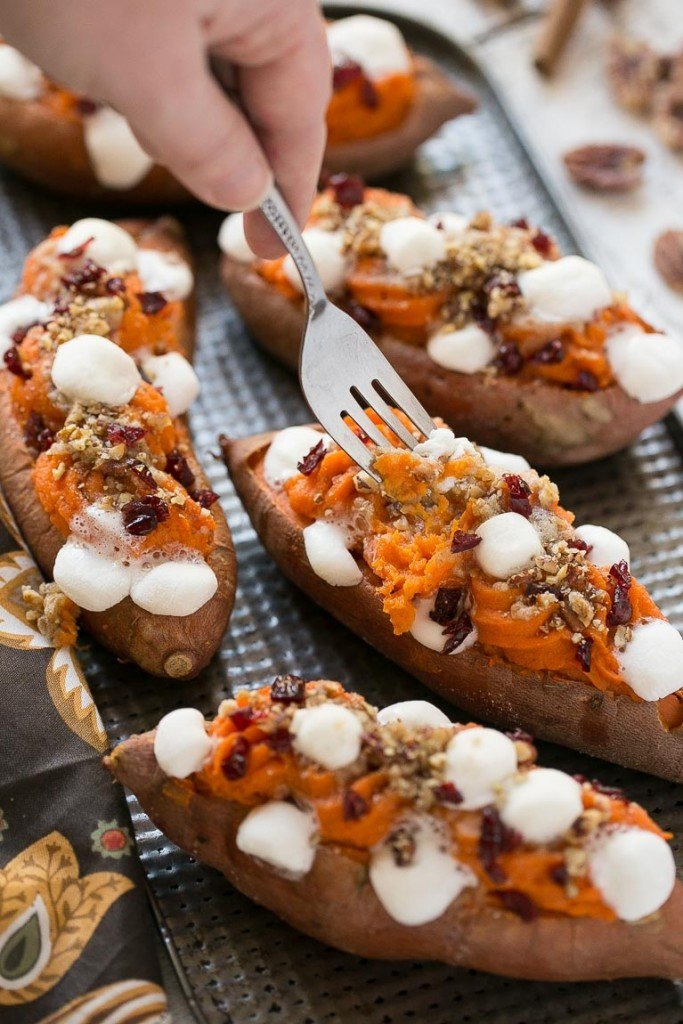 These loaded twice baked sweet potatoes are piled high with pecan brown sugar streusel, marshmallows and dried cranberries. You can prepare them in advance and then pop them in the oven right before your holiday meal!