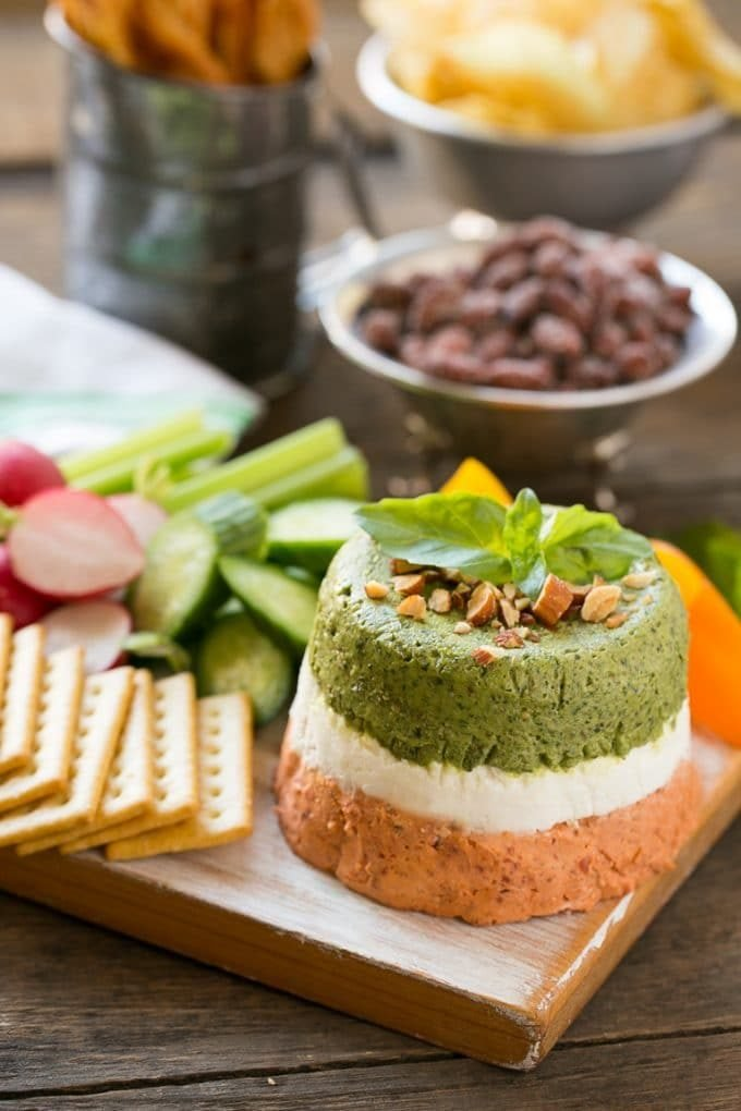 Layered pesto dip served with crackers and vegetables.