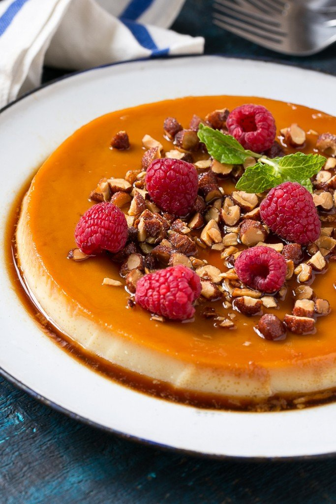 This rich and creamy flan is flavored with vanilla and almonds and is finished off with chopped honey roasted almonds and raspberries.