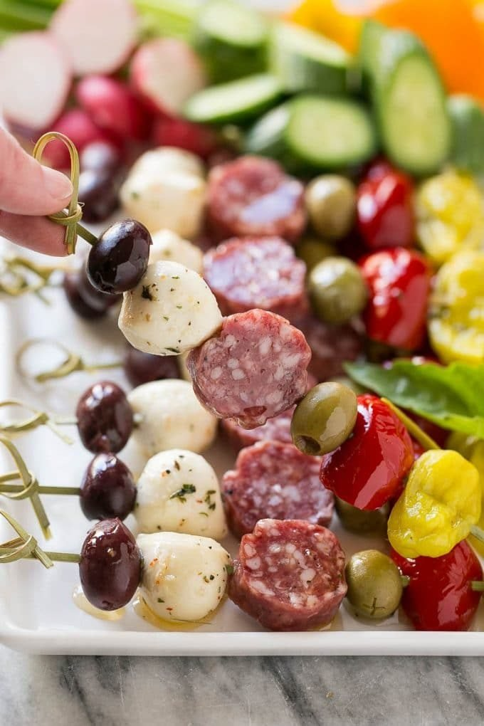 A hand holding up a skewer of salami, cheese and olives.