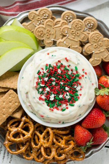 This Christmas cookie dough dip has a fluffy and creamy base that's swirled with plenty of holiday sprinkles and served with fruit and cookies for dipping. It only takes 5 minutes to make! #HolidayWithChobani Ad