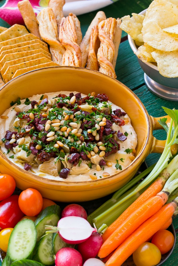 This mediterranean layered dip starts with a base of whipped feta cheese and is topped with artichokes, olives, sun dried tomatoes and pine nuts. Ready in about 10 minutes, it's the perfect party appetizer!