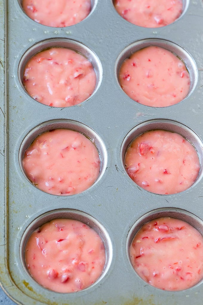 Cherry muffin batter inside muffin tins.