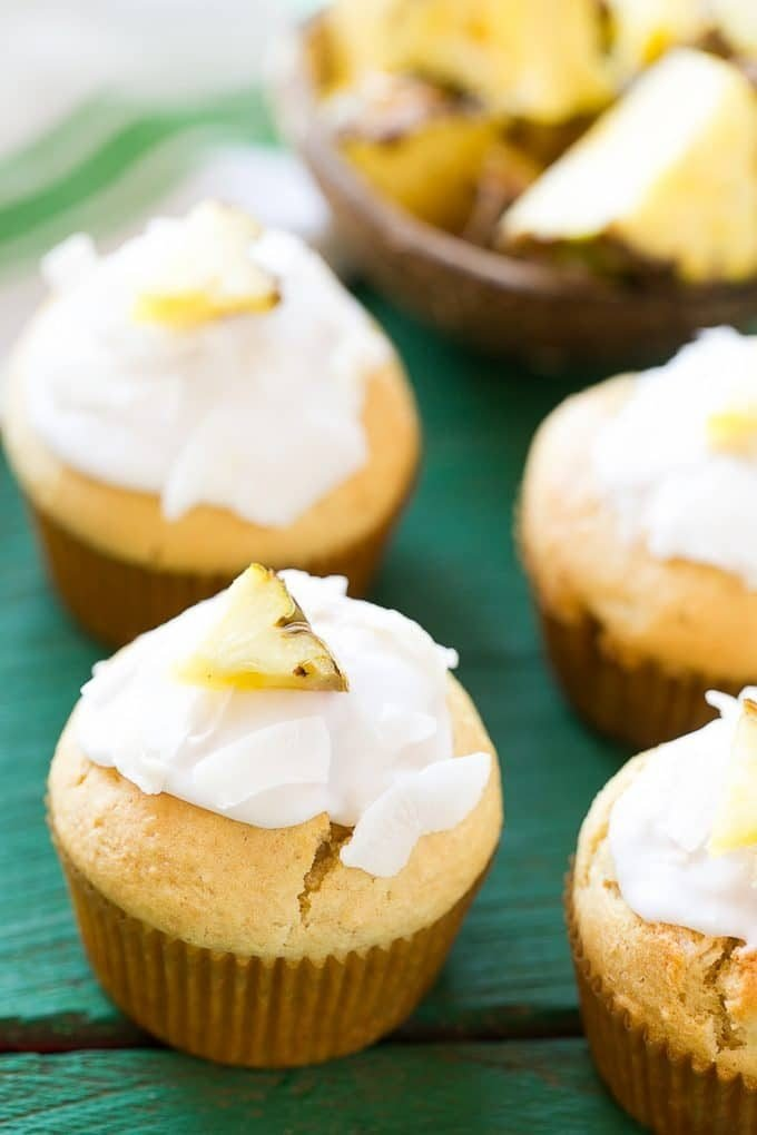Coconut muffins topped with shredded coconut and pineapple.