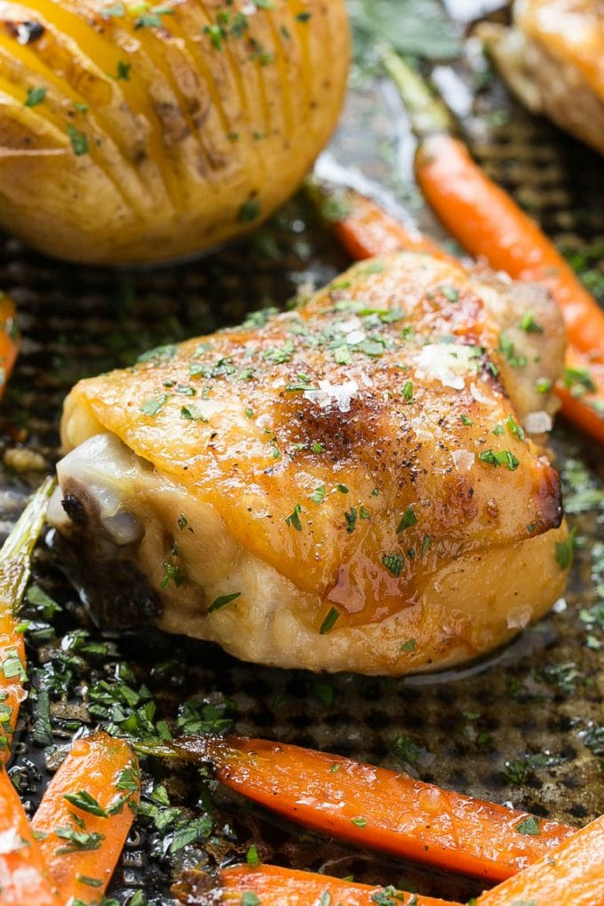 A roasted chicken thigh surrounded by carrots and potatoes.