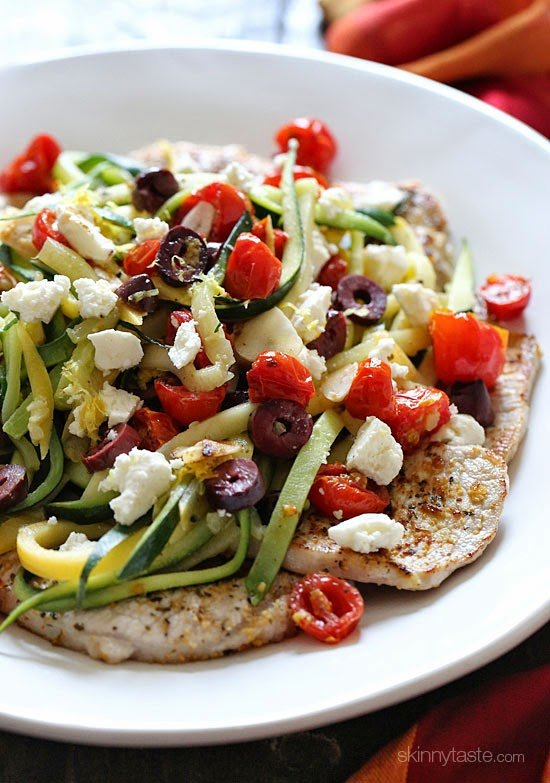 Boneless pork chops topped with tomatoes, olives and zucchini.