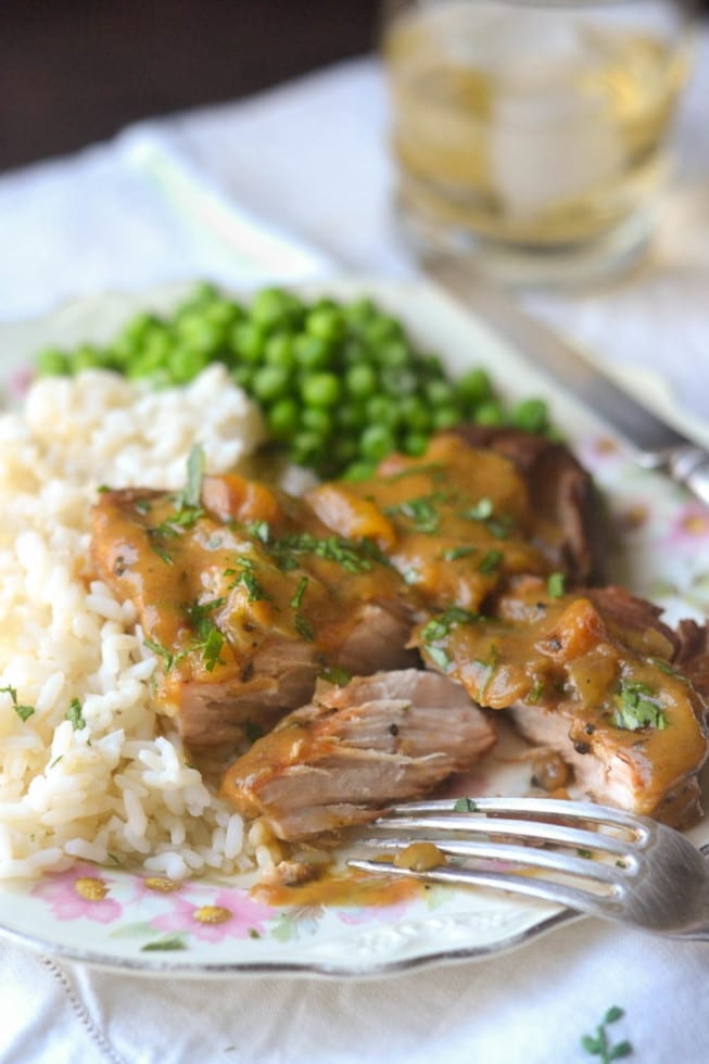 Pork chops over rice with a side of peas.