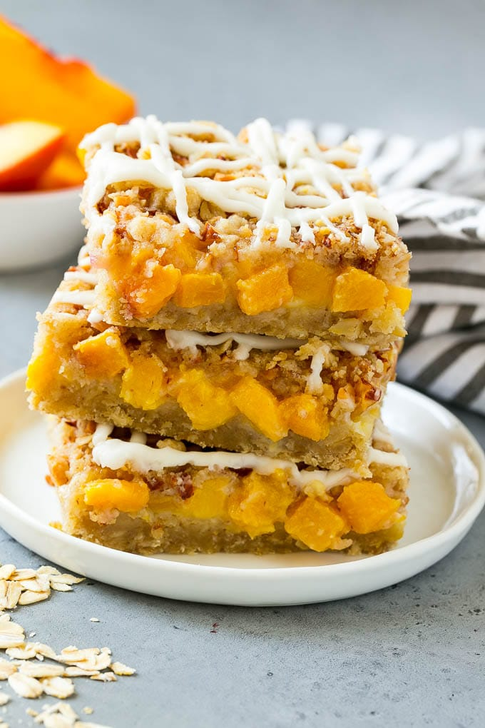 A stack of peach crumble bars topped with vanilla glaze.