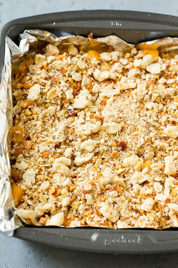 A pan of unbaked peach crumble bars.
