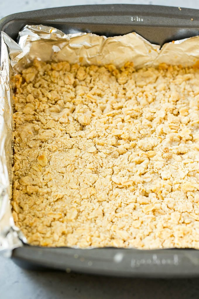 An oatmeal and brown sugar crust pressed into a pan.