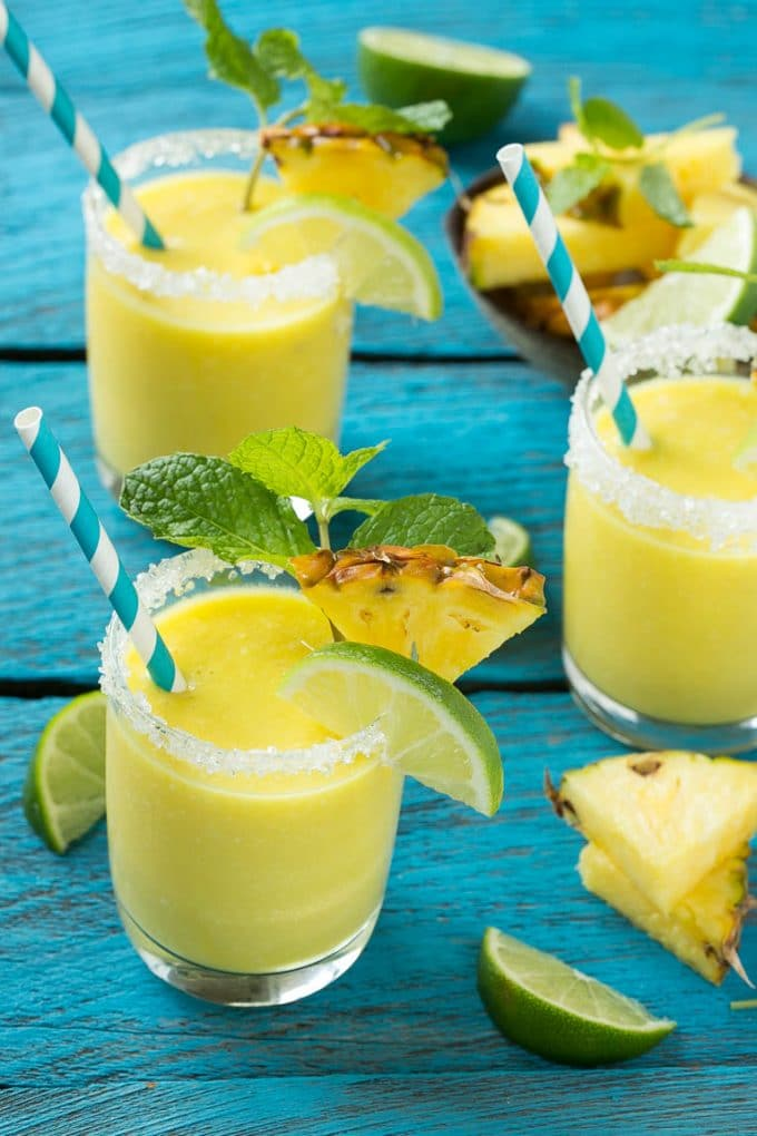 Glasses of pineapple coconut smoothie garnished with limes and mint.
