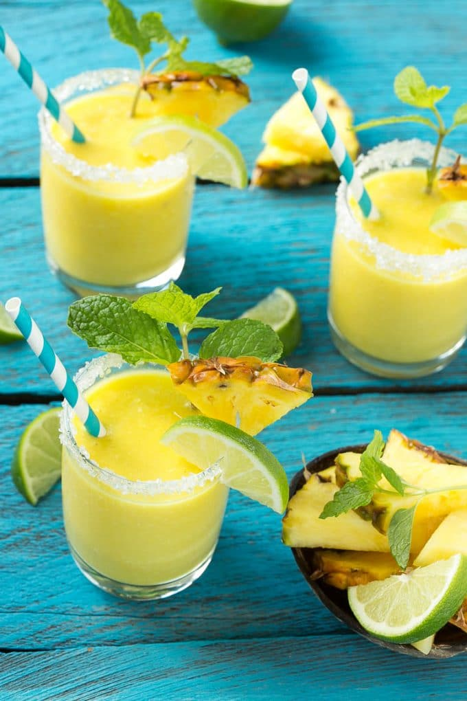 Pineapple coconut smoothies in glasses with sugared rims.