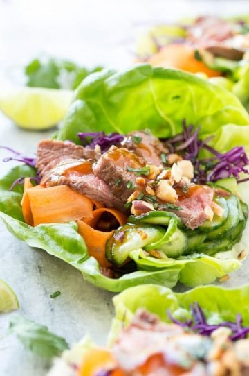 This recipe for beef lettuce wraps is seared steak layered with fresh vegetables and pickled cucumbers inside of cool lettuce cups and finished off with an Asian sauce, chopped almonds and fresh herbs. #CAonMyPlate #CultivateCA