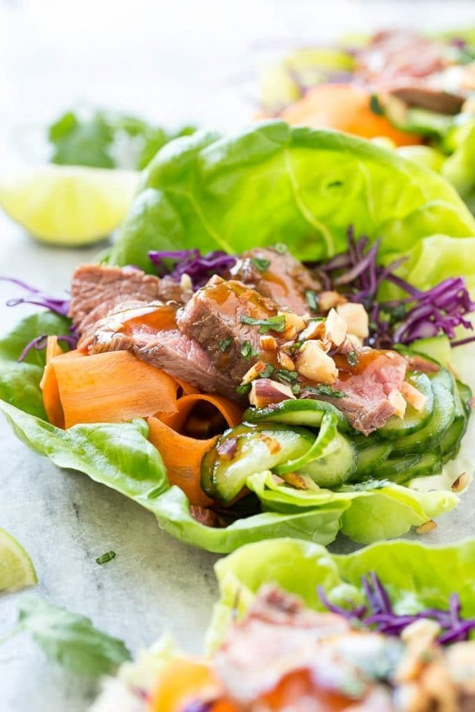 Beef lettuce wraps with seared steak, carrots, cucumbers and savory sauce.