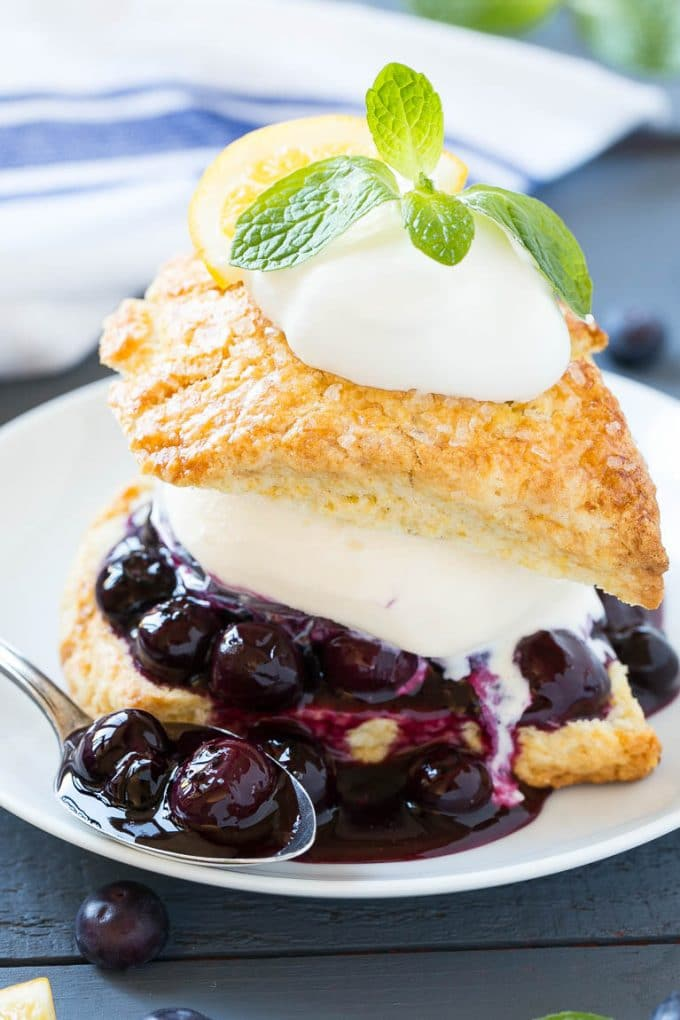 This recipe for blueberry shortcake is vanilla ice cream and homemade blueberry sauce sandwiched between lemon shortcake and finished off with whipped cream. This easy and elegant dessert is perfect for any occasion!