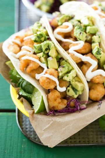 This recipe for fried shrimp tacos is a pile of crispy shrimp that's layered with cilantro lime cabbage slaw and avocado relish then stuffed inside warm flour tortillas. It's a quick and easy meal that tastes like it came from a restaurant! #ShrimpItUp ad