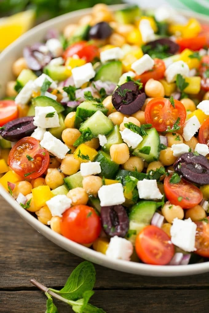 Cucumbers, chickpeas, olives, tomatoes, peppers and feta cheese in a serving bowl.