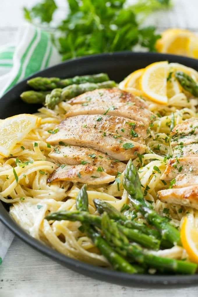 A skillet with lemon asparagus pasta, cream sauce and sliced grilled chicken.