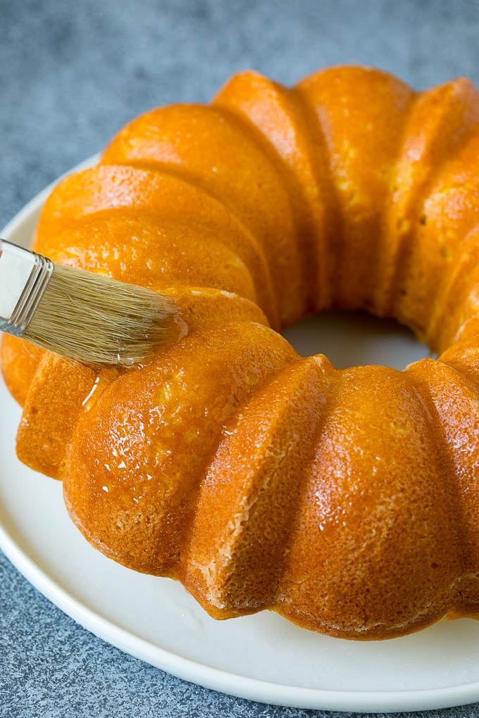 A brush adding lemon syrup to a bundt cake.