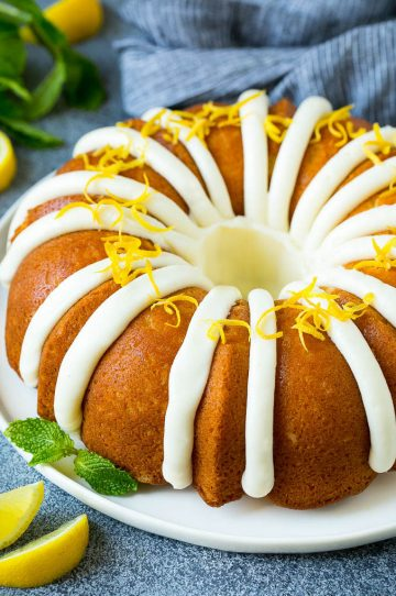 A lemon bundt cake topped with cream cheese frosting and lemon zest.