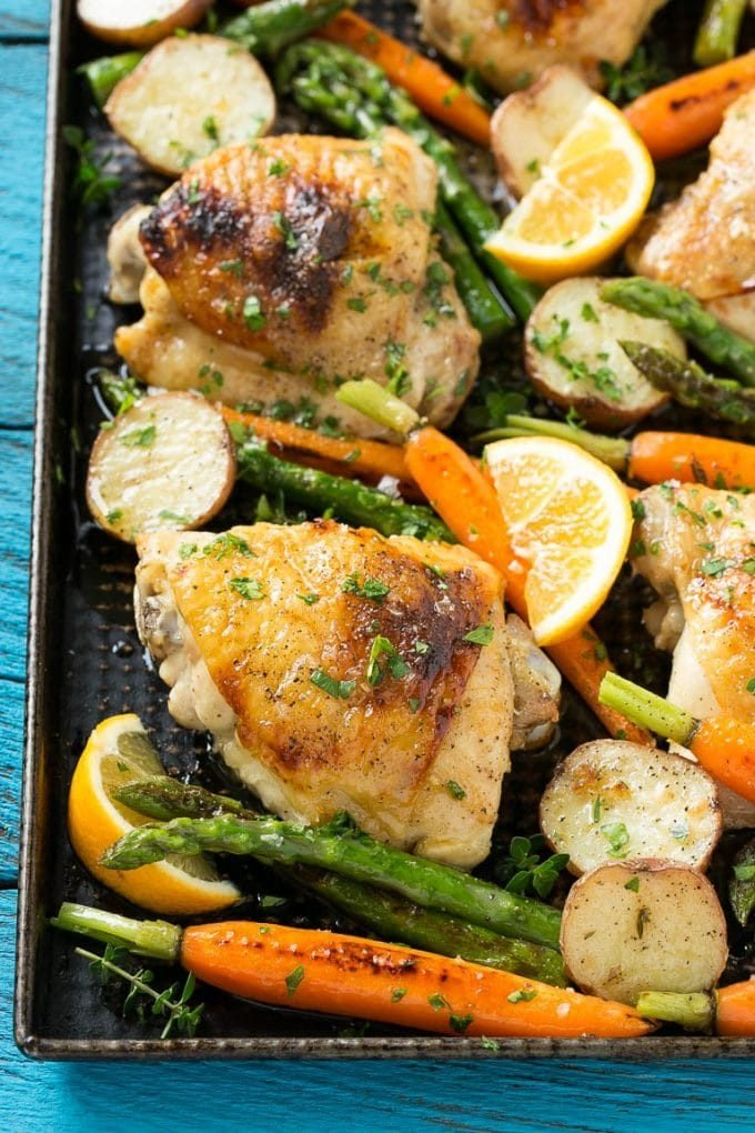 A sheet pan full of lemon thyme chicken thighs, potatoes and vegetables.
