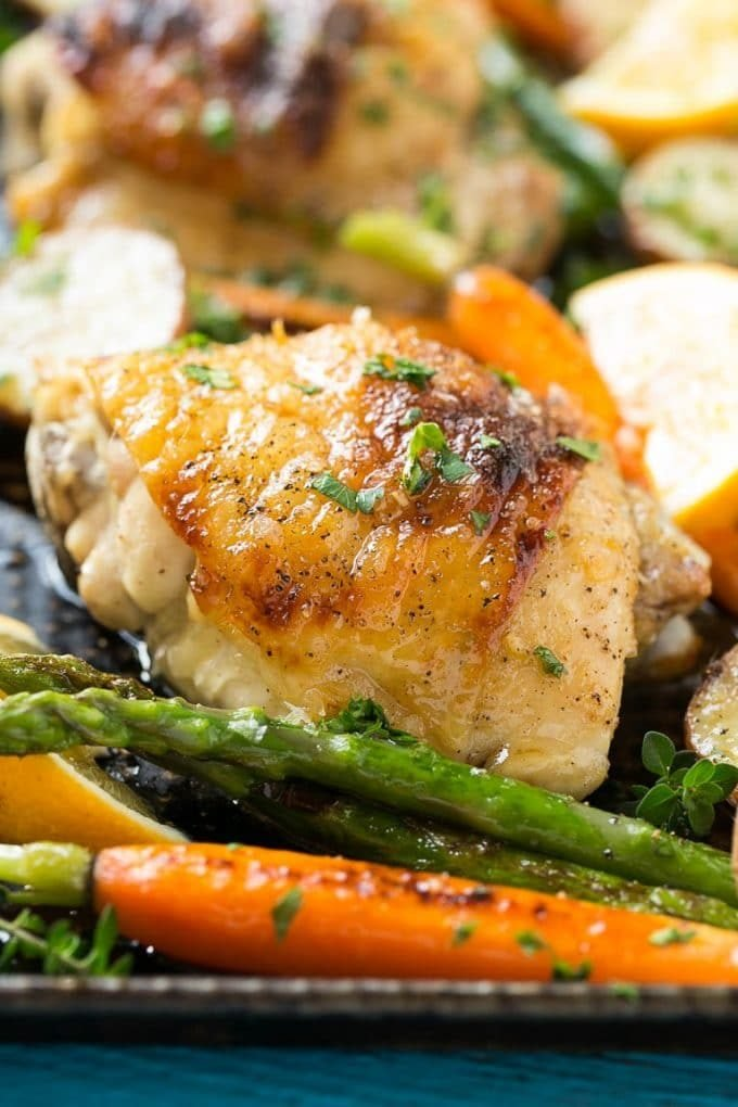 Lemon thyme chicken on a sheet pan with asparagus and carrots.