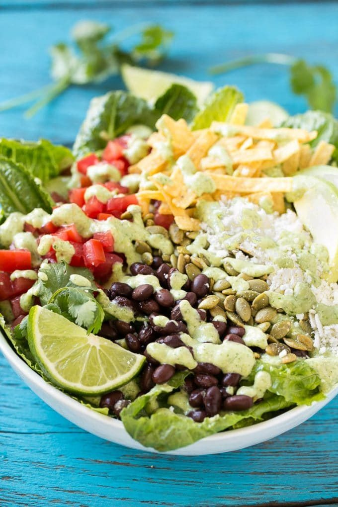 Creamy cilantro dressing drizzled over a bowl of Mexican Caesar salad.